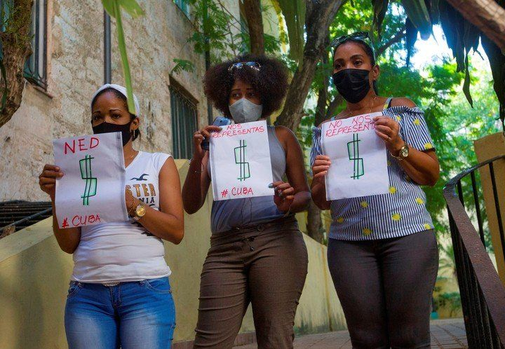 Three women with symbolic posters against the opposition and playwright Yunior García.  Photo EFE